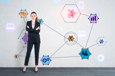 Smiling young businesswoman wearing black suit standing with crossed arms near concrete wall with colorful internet icons drawn on it. Concept of hi tech in business