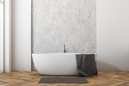Interior of minimalistic bathroom with white and concrete walls, wooden floor, large window and white bathtub with towel on it and gray rug near it. 3d rendering