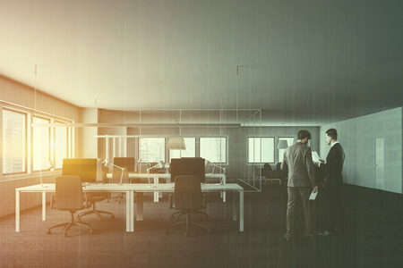 Two businessmen in interior of modern office with rows of white computer tables with gray chairs, office lounge with round tables and meeting room in the background. Toned image double exposure Archivio Fotografico