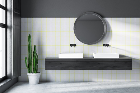 Interior of modern bathroom with gray and white tile walls, concrete floor, double sink standing on black wooden countertop and round mirror. 3d rendering Stock Photo