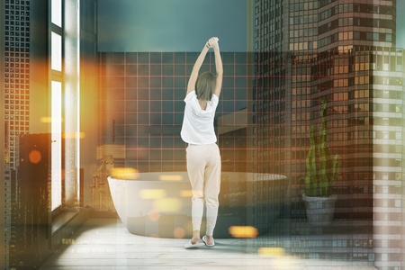 Woman standing in modern bathroom with gray and black tile walls, wooden floor and big gray bathtub near the window. Toned image double exposure