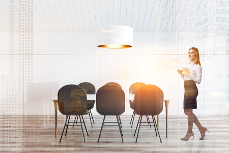 Woman in interior of attic dining room with white walls and ceiling, wooden floor and long table with gray chairs with massive ceiling lamp above it. Toned image double exposure