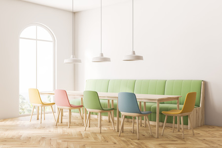 Corner of modern cafe with white walls, wooden floor, arched window, long green sofa and square wooden tables with pastel colored chairs. 3d rendering Stock Photo