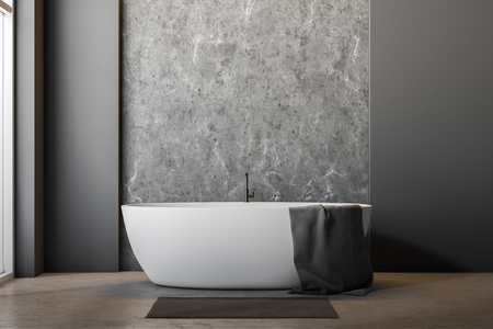 Interior of minimalistic bathroom with gray and concrete walls, concrete floor, large window and white bathtub with towel on it and gray rug near it. 3d rendering
