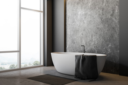 Corner of minimalistic bathroom with gray and concrete walls, concrete floor, large window and white bathtub with towel on it and gray rug near it. 3d rendering