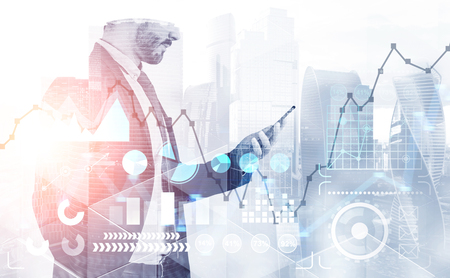 Side view of unrecognizable bearded businessman looking at his smartphone standing in modern city with double exposure of business infographics interface. Toned image