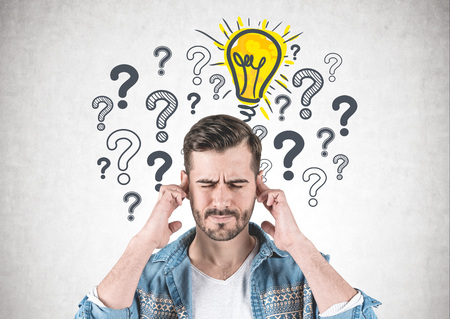 Portrait of bearded young man wearing jeans shirt and thinking hard with eyes closed and fingers on temples standing near concrete wall with many question marks and lightbulb drawn on it Imagens