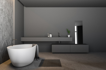 Side view of modern bathroom with gray and concrete walls, concrete floor, white bathtub with towel on it and long gray sink with mirror. 3d rendering Archivio Fotografico - 117071275