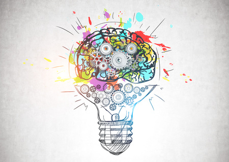 Colorful brain sketch with gears and cogs drawn inside light bulb on concrete wall. Concept of creative thinking