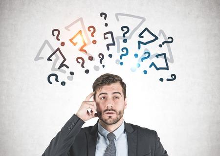 Jeune homme d'affaires à la barbe portant un costume sombre et pensant avec son doigt près du temple debout près d'un mur de béton avec des points d'interrogation dessinés dessus.