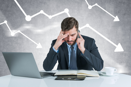 Serious young businessman sitting at office table with laptop, looking at documents and talking on smartphone. Concrete wall background with falling graphs