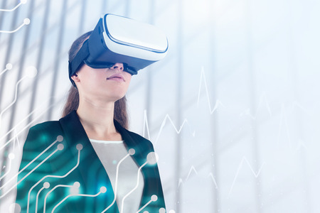 Beautiful young businesswoman wearing black suit and vr glasses standing over skyscraper background with double exposure of circuits and graphs. Toned image
