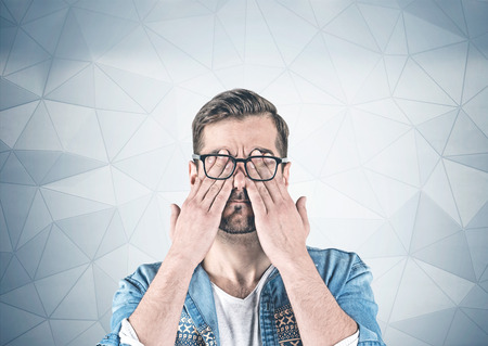 Portrait of bearded young man in casual clothes and glasses covering his eyes with hands standing near geometric pattern wall. Concept of tiredness Фото со стока