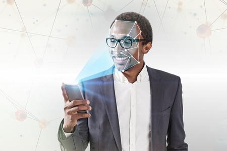 Sonriente empresario afroamericano en gafas con smartphone con tecnología de reconocimiento facial sobre fondo blanco con polígonos. Doble exposición de imagen tonificada Foto de archivo