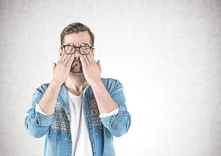 Portrait of bearded young man in casual clothes and glasses covering his eyes with hands standing near concrete wall. Concept of tiredness. Mock up