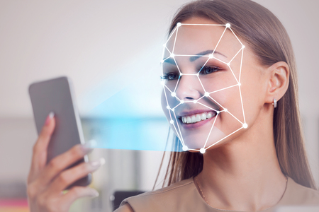 Smiling blonde businesswoman using smartphone with face recognition technology in blurred office. Toned image double exposure
