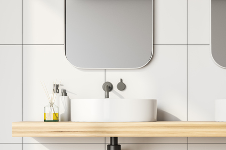 Close up of bathroom sink standing on wooden shelf with mirror above it in room with white tile walls. 3d rendering