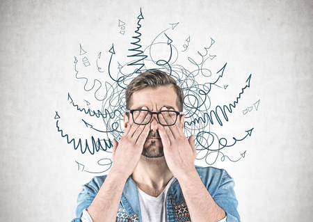 Portrait of bearded young man in casual clothes and glasses covering his eyes with hands standing near concrete wall with arrows drawn around his head. Concept of decision making