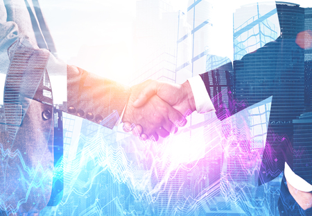Close up of two businessmen shaking hands over skyscrapers background with double exposure of bright graphs. Stock market concept. Toned image