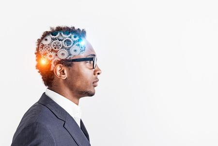 Widok z boku surowy młody biznesmen Afroamerykanów w okularach i garniturze z mózgiem narzędzi wewnątrz jego głowy. Tło białe ściany. Makieta