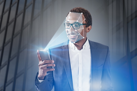 Smiling African American businessman in glasses using smartphone with face recognition technology over skyscraper background. Toned image double exposure