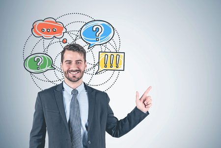 Portrait of smiling young bearded businessman wearing dark suit and pointing with his finger standing near concrete wall with colorful decision making sketch on it. Mock up