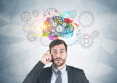 Young businessman with beard wearing dark suit and thinking with his finger near temple standing near geometric pattern wall with brain with cogs drawn on it.