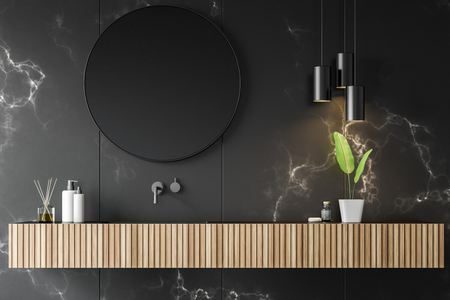 Close up of wooden bathroom sink with round mirror above it located in room with black marble walls and original lamps. 3d rendering Stock Photo