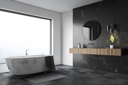 Corner of luxury bathroom with white and black marble walls, large window, black tiled floor, white marble bathtub and wooden sink with round mirror. 3d rendering Banco de Imagens - 118227630