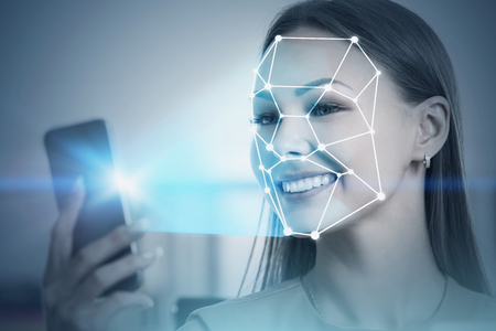 Smiling blonde businesswoman in dress using smartphone with face recognition technology in blurred office. Toned image double exposure