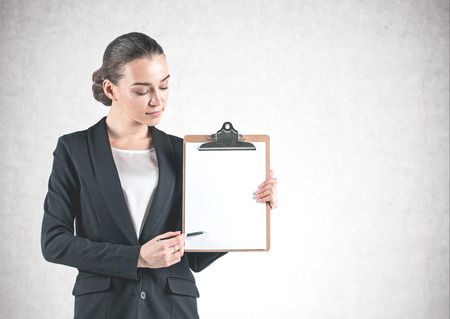 Portrait of young businesswoman wearing black suit and pointing at her clipboard with pen standing near concrete wall. Mock up Stockfoto