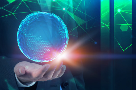 Hand of young businessman holding planet hologram with network interface. Dark blue background. Concept of digital world. Double exposure toned image