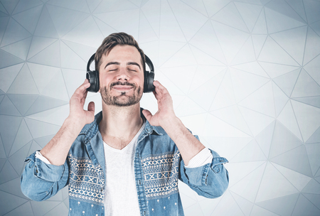 Portrait of young man in casual clothes listening to music in headphones with closed eyes. Geometric pattern wall background. Concept of relaxation. Mock up Imagens