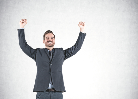 Portrait of smiling young businessman celebrating victory and standing with arms in the air near concrete wall. Mock up Banque d'images - 118899089