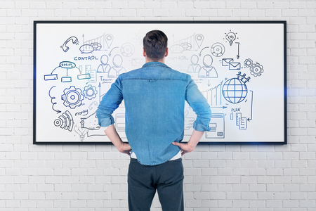 Rear view of caucasian young man in jeans shirt and gray pants looking at whiteboard with business plan sketch on it. Toned image