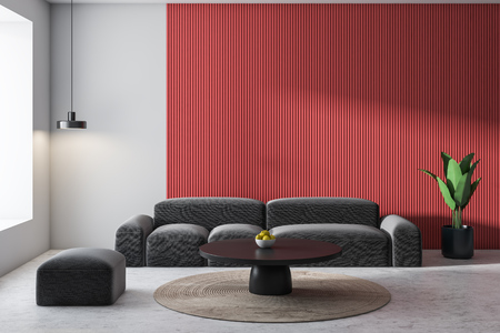 Interior of modern living room with white and red walls, concrete floor, comfortable gray sofa and small pouf standing near black coffee table.3d rendering