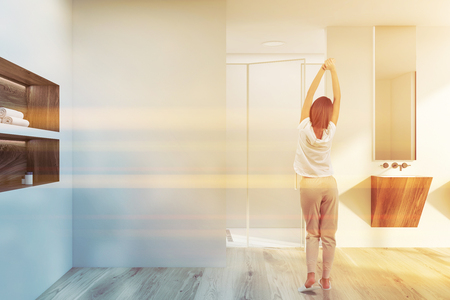 Young woman standing in modern bathroom with white walls, wooden floor, sink with mirror above it and glass door shower. Wooden shelves with towels. Toned image