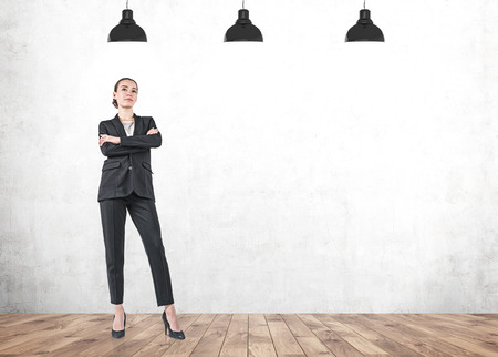 Full length portrait of serious young businesswoman standing with crossed arms and thinking over concrete wall background. Mock up