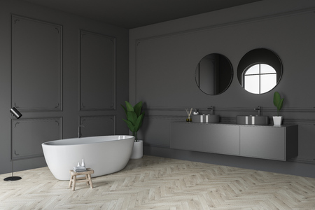 Corner of luxury bathroom with gray walls, light wooden floor, white bathtub and double sink on gray countertop with round mirrors above it. 3d rendering Фото со стока
