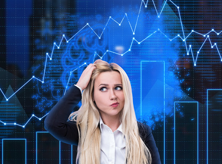 Confused young blonde businesswoman standing over dark blue background with blurred brain sketch and business graphs. Concept of business strategy Stock Photo