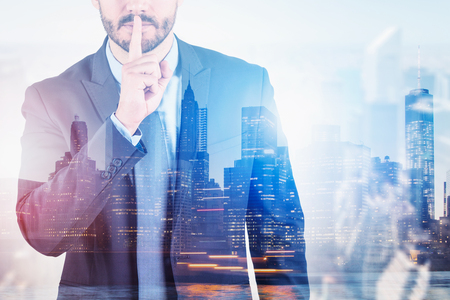 Unrecognizable man in suit making hush gesture standing over cityscape background. Corporate secret concept. Toned image double exposure