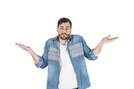 Portrait of young confused handsome man giving I dont know gesture on white background