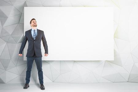 Portrait d'un jeune homme d'affaires confiant debout avec les poings serrés près du mur avec une affiche vide et regardant vers le haut. Notion de publicité. Maquette