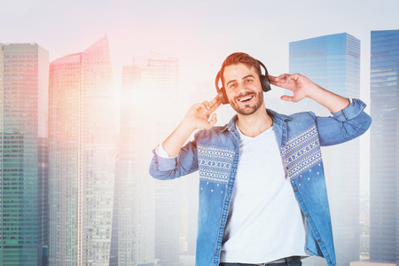 Smiling young man in headphones and casual clothes enjoying listening to music standing over skyscrapers background. Toned image