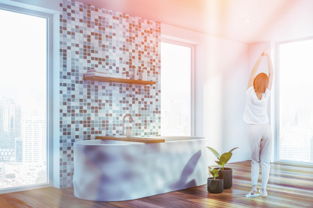 Rear view of woman in pajamas standing in comfortable bathroom with tiled walls, tall windows and white bathtub. Toned image