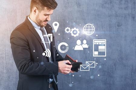 Triste jeune homme d'affaires regardant dans son portefeuille vide, debout près du mur de béton. Hologramme d'icônes Internet. Concept d'échec de l'entreprise électronique. Image tonique double exposition