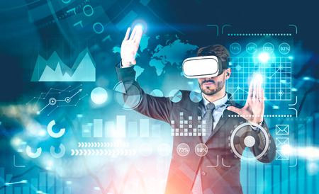 Businessman in VR glasses working with global business infographics interface. Concept of hi tech. Toned image double exposure. Elements of this image furnished by NASA
