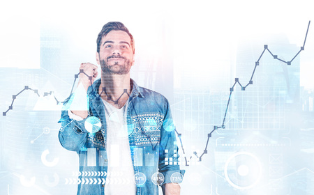 Smiling man in casual clothes celebrating financial victory over modern city background with double exposure of business infographic and graphs. Startup concept. Toned image 免版税图像