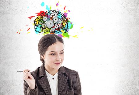 Durchdachte junge Geschäftsfrau mit Stift lächelnd in der Nähe der Betonmauer mit buntem Gehirn mit darauf gezeichneten Zahnrädern. Attrappe, Lehrmodell, Simulation Standard-Bild