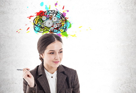Thoughtful young businesswoman with pen smiling standing near concrete wall with colorful brain with gears drawn on it. Mock up